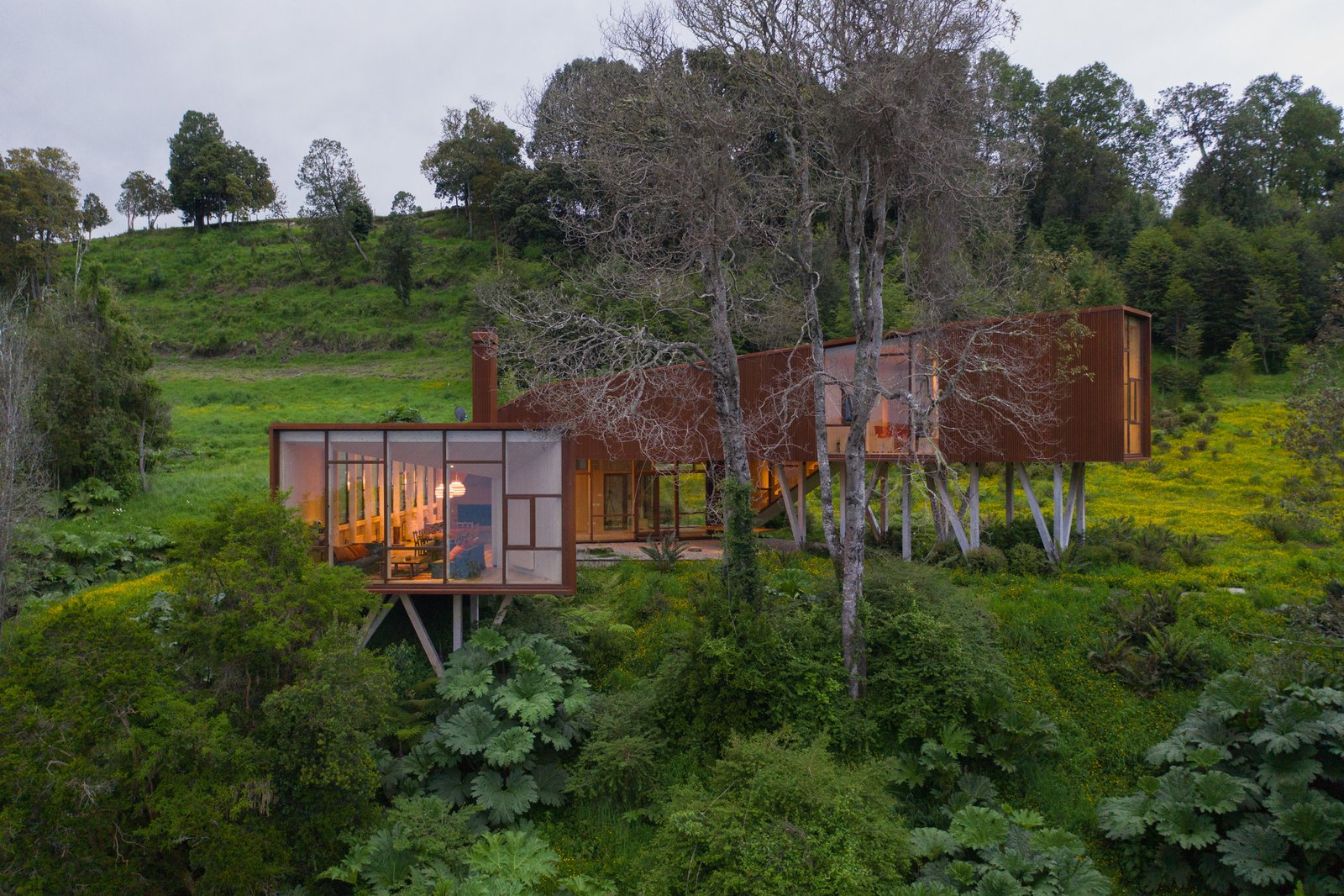 A robust Cor-Ten steel home rises from the rugged landscape.