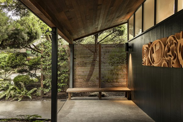 A built-in bench sits outside the entry. The tongue-and-groove siding is painted a rich charcoal.
