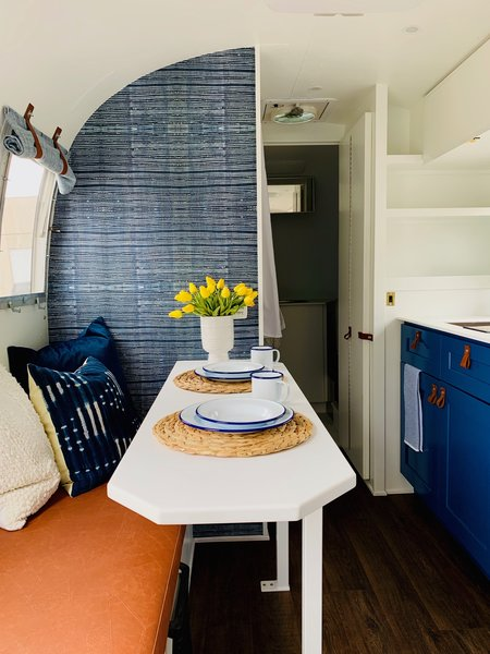 "In the eating area of a 1966 Airstream Safari, ""a custom table for two provides not only an eating space but also a deep bench to hang out on and watch the TV that is mounted on the opposite wall,"" explains Cole. The bench is upholstered with a faux leather, helping ensure any spills are easy to clean up."