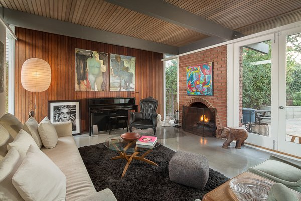 Original details in the living room include wood-clad walls and ceilings, a wood-burning fireplace, and exposed beams. French doors open up to a patio area.