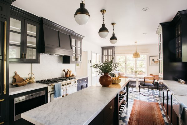 Featuring a timeless color palette, the oversized kitchen includes marble countertops, Granada concrete tile, and a handcrafted La Cornue stove.
