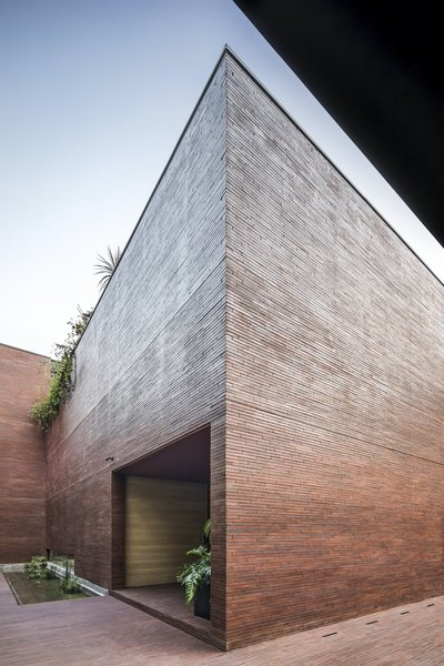 """The entire home is wrapped in a brick """"skin"""" that extends onto the ground at the front and sides of the home. The entrance is found through a simple void in the facade beside a pond with floating vegetation that hints at the verdant interior."""