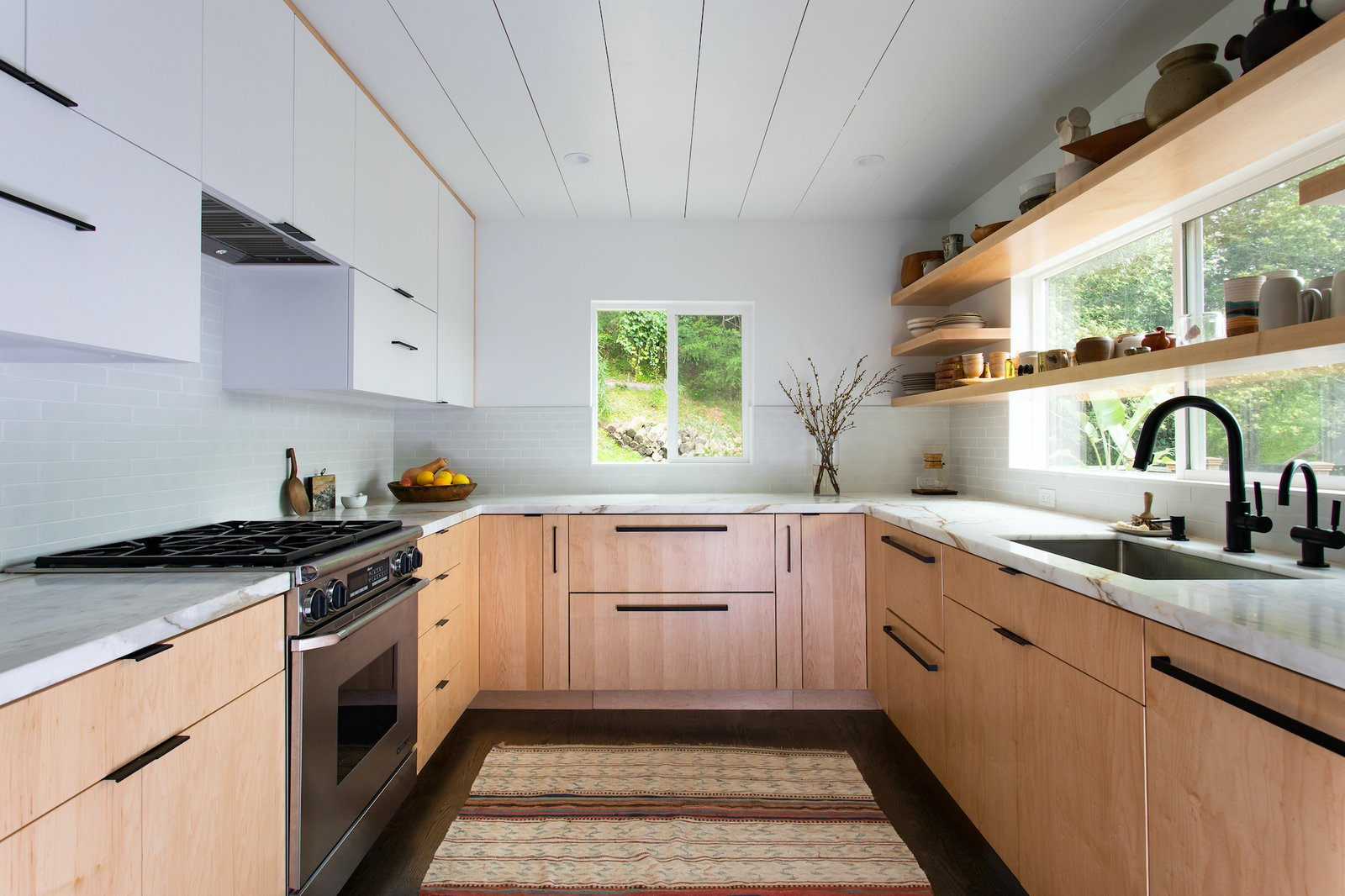 """Shands paired maple wood kitchen cabinets with veined marble countertops to provide character to the space without overwhelming it. """"These materials, complemented by the open shelves with stacked ceramics, are key to the experience,"""" she says. Sub-Zero undercounter refrigerators and freezer opened the kitchen up to allow for more counter space."""
