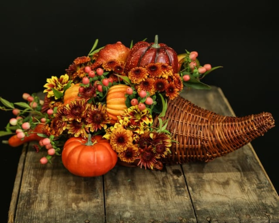 a cornucopia filled with flowers and fall accessories