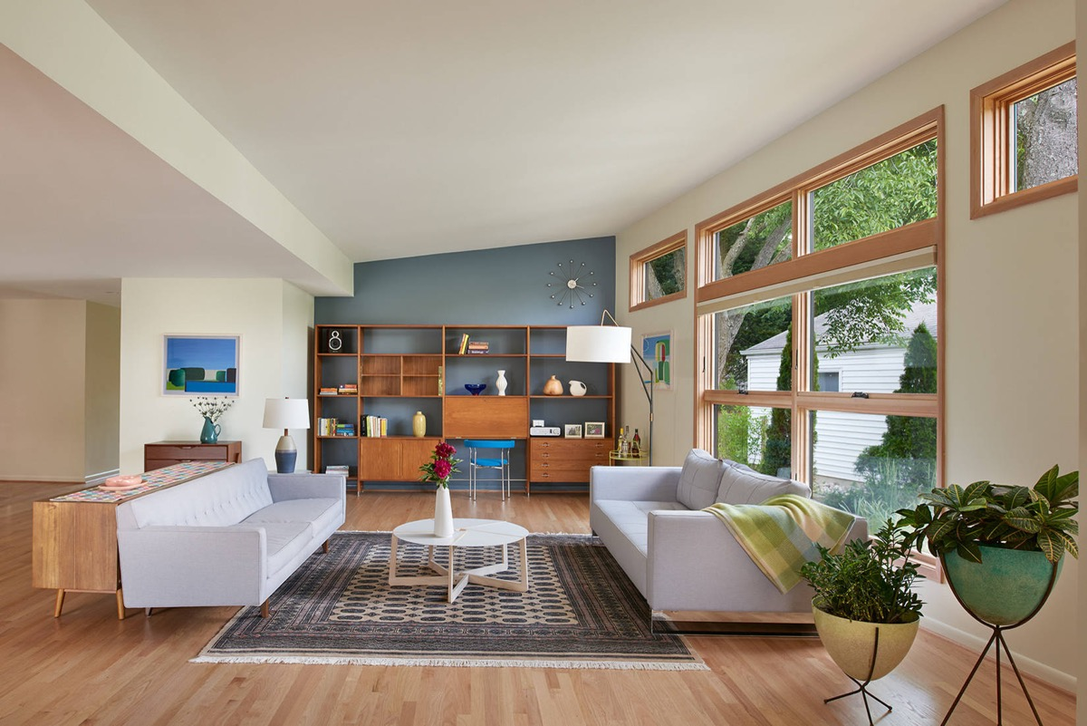 mid century modern living room with white couches and geometric console