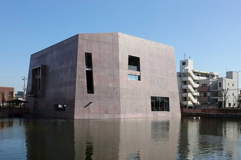monolithic library extension by maru architecture floats on serene pond in matsubara, japan